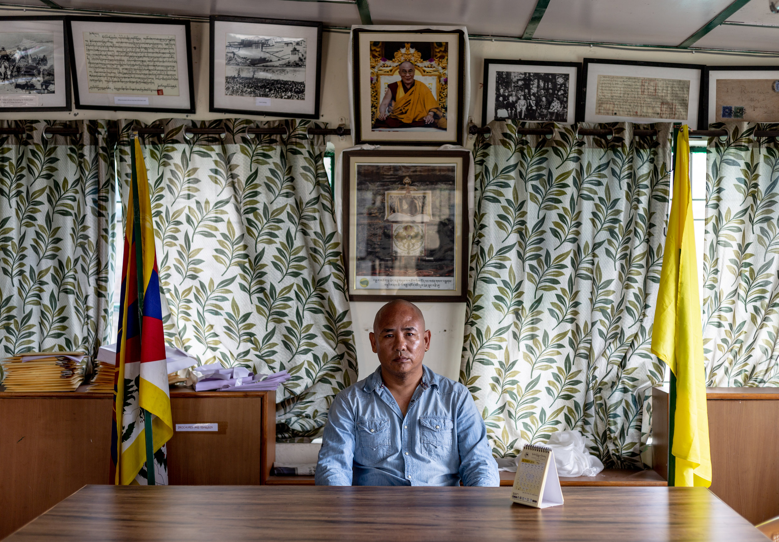 Lobsang Tsering, vice-president of the Tibetan Youth Congress, sitting in the organization's office. The portrait of the Tibetan spiritual leader, the Dalai Lama, hangs on the wall behind him. Photo by Avinash Giri.