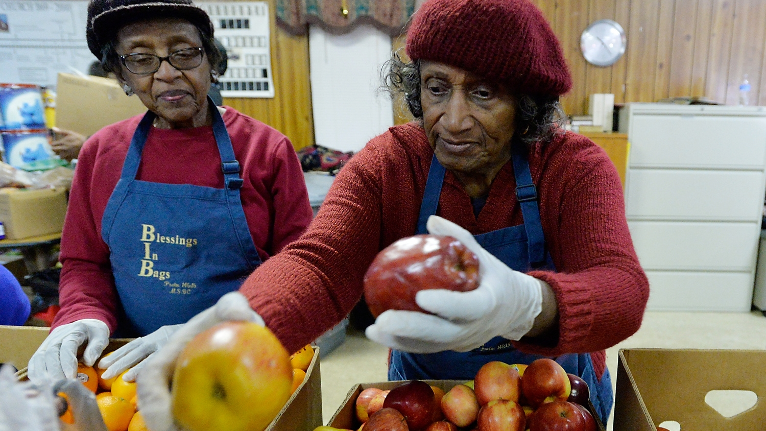 Volunteer Alene Dixon, alongside Doris Alston, hands out free, fresh apples to those in need of food at the Martin Street Mobile Market in Raleigh, N.C. on Saturday, December 10, 2016. The Inter-Faith Food Shuttle provides some of the fresh food for market. (Photo by Sara. D. Davis)