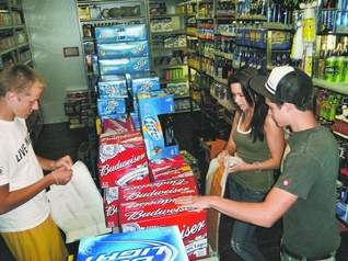 "Kensington Woods High School students, from left, Colin McElhone, Lauren Stockelman and Sean Nichol place bright-yellow stickers that read, in part, ""Providing Alcohol to Minors Is Illegal,"" on multipacks of alcohol at a Livingston County store June 10. (SUBMITTED PHOTO)"