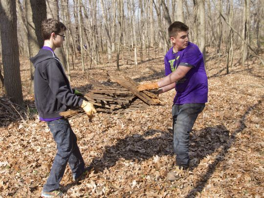 Kensington Woods 10th grader Isaac Provencher, left, and seventh grader Nathan Picano clear wood debris from the woods of Strawberry Point Nature Preserve in Hamburg Township as part of the school's day of service. (Photo: Gillis Benedict/Livingston Daily)