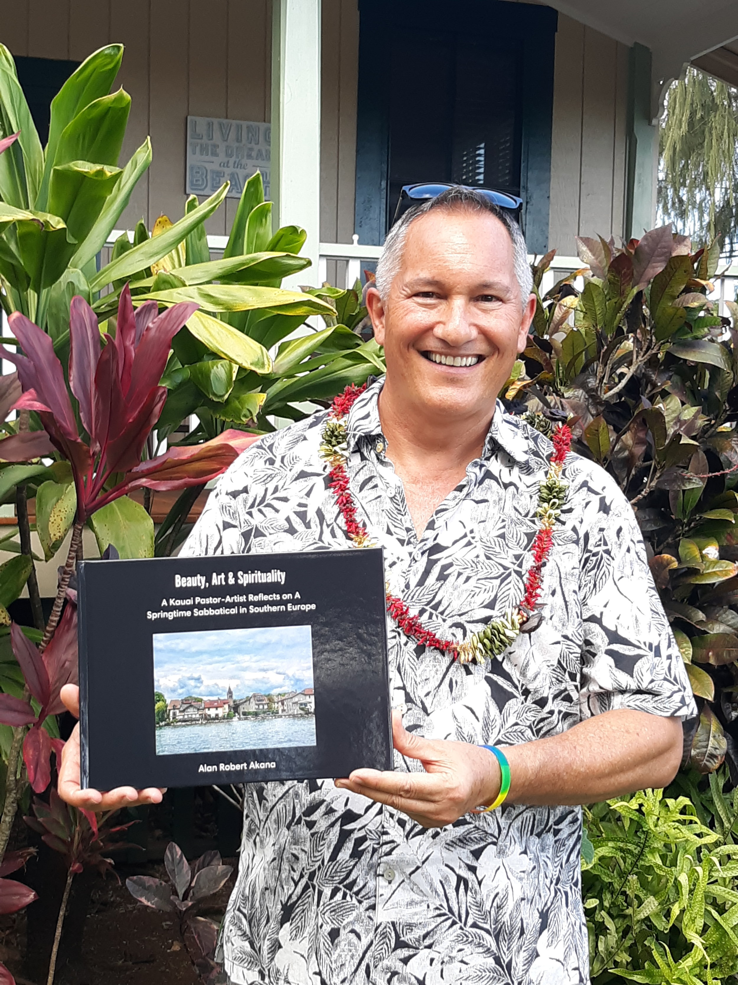 Alan displays a copy of his latest book amidst the healthy red and green tropical foliage that fronts the large, welcoming lanai of the charming 1928 Smith Memorial Parsonage. The historical building and grounds are owned and maintained by Koloa Union Church and serve as the residence for the church's kahu (pastor).