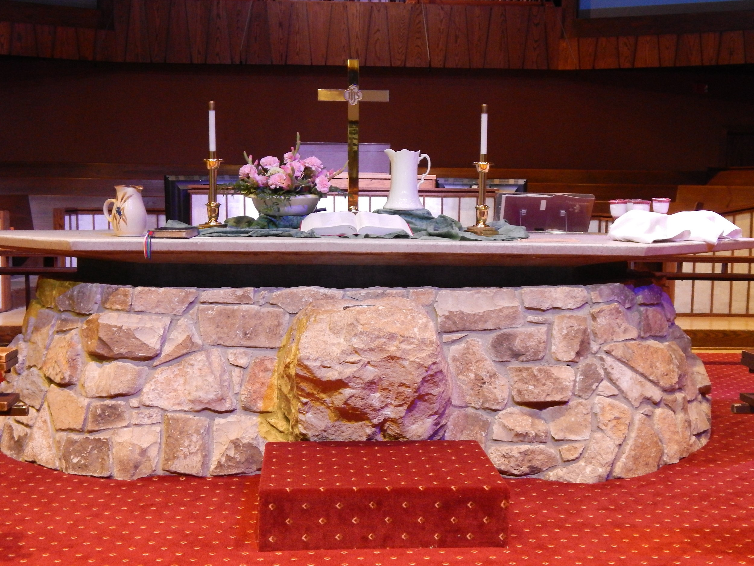 "ALTAR - Conspicuous by its size and location is the great freestanding stone ALTAR, designed so that people can gather around it as the center of sacrifice.  The two United Methodist sacraments, Baptism and Holy Communion, are keys to this area's use.  The Baptismal Font is attached to the front of the altar and the communion rail extends around the altar so that the participants can become ""a family of God gathered around the Lord's table""."