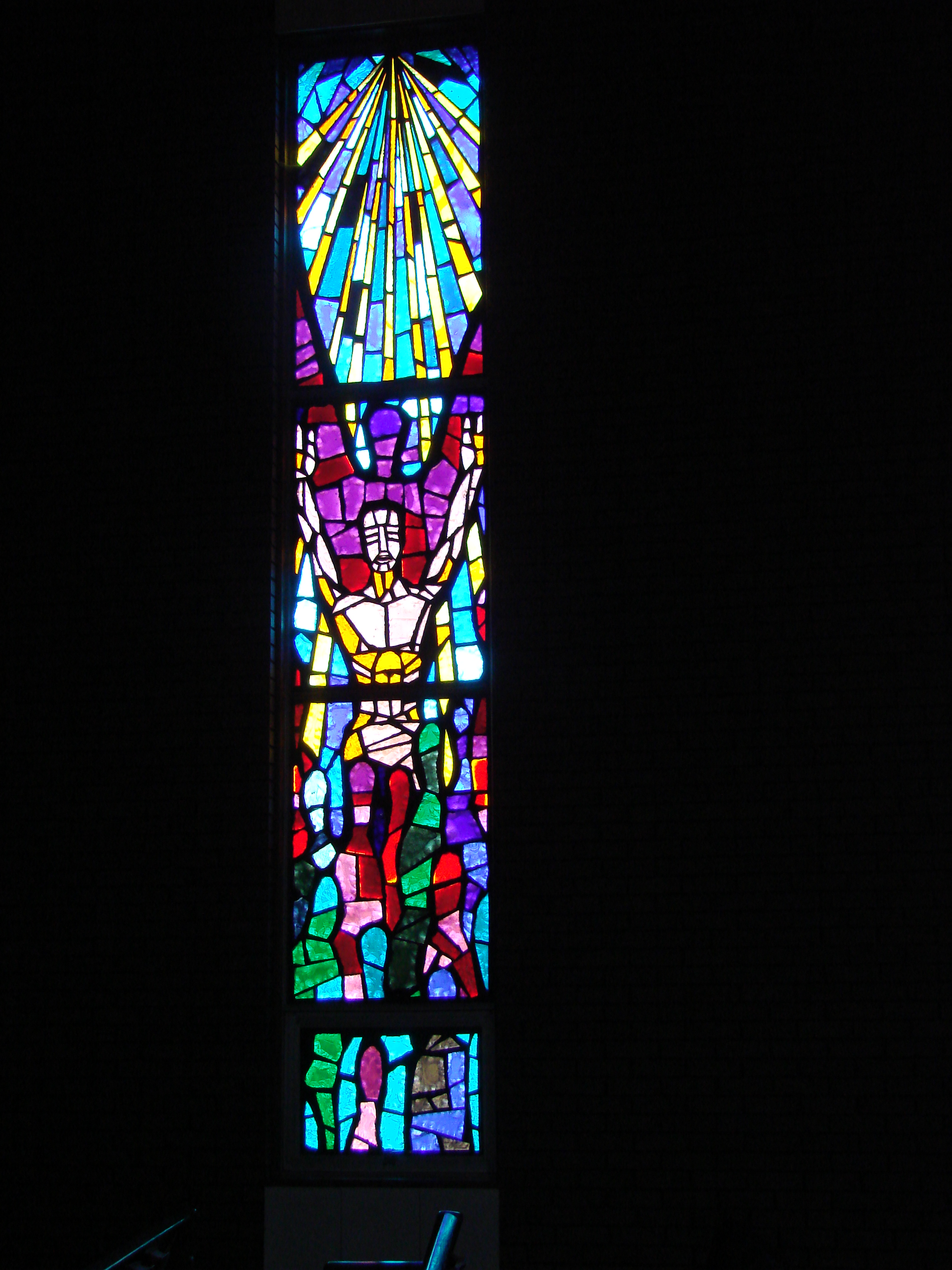 HUMANKIND WINDOW - The first long window was designed to symbolize how God's message works through HUMANKIND.  In the lower part is a human figure reaching upward.  God speaks to us through our bodies.  Immediately above and behind this figure is another figure with a color purple.  This symbolizes the mind.  Above these two figures are the artistic lines to symbolize Spirit, descending upon humankind.  This window's theme was chosen to remind us that the messages we get during worship reach us through body, mind, and spirit.