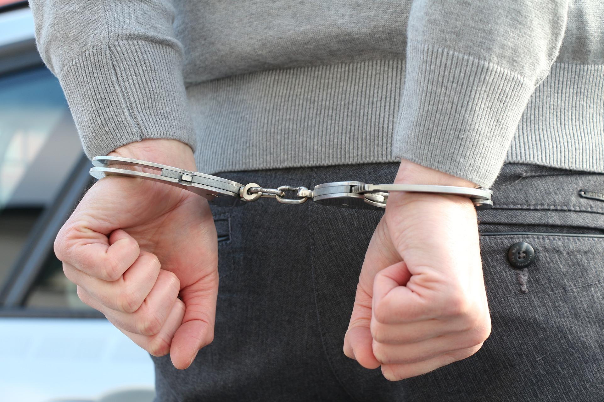 Man in handcuffs needing a criminal defense attorney