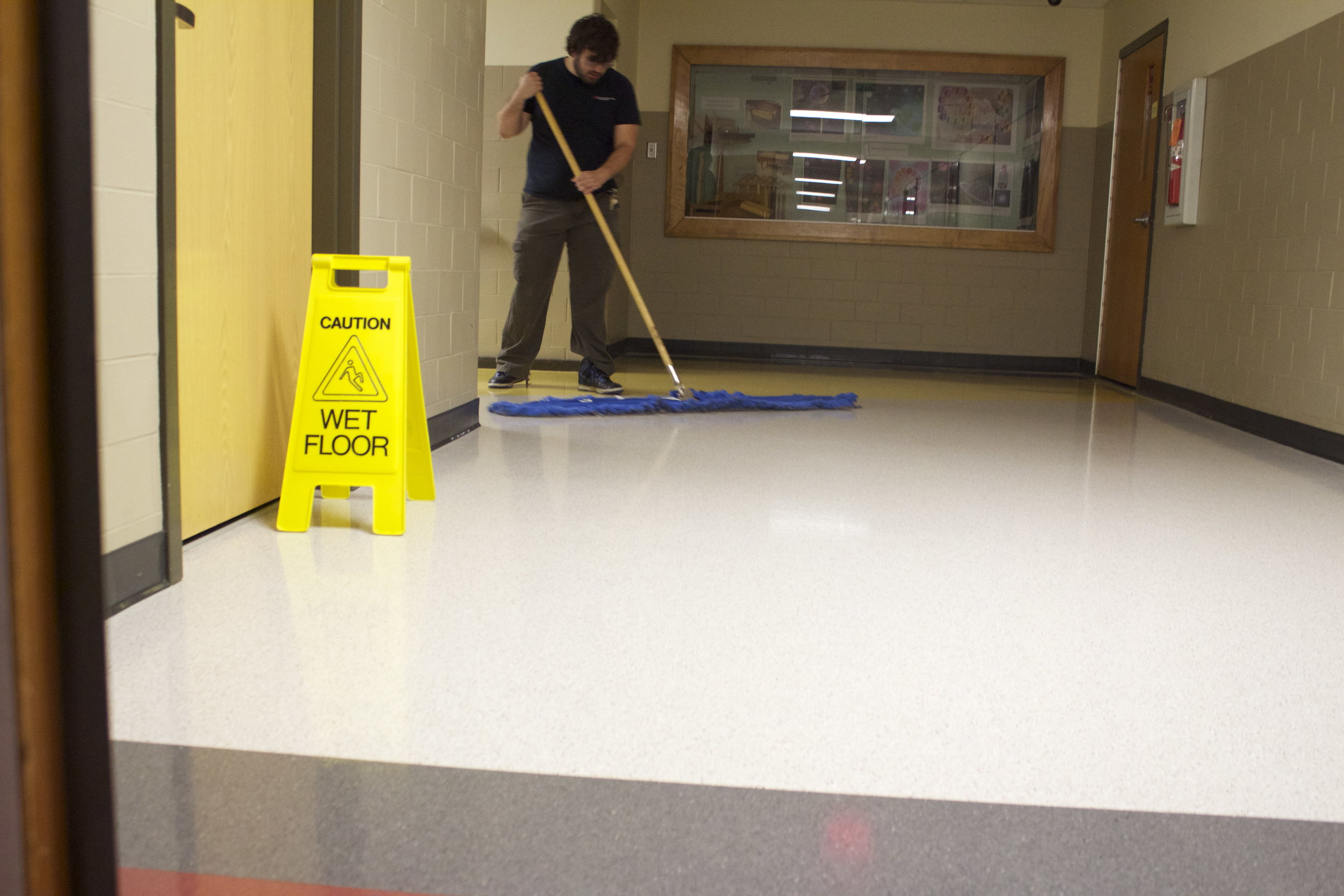 Man mopping a wet floor in a business where someone is about to slip and fall and in need of a premises liability attorney
