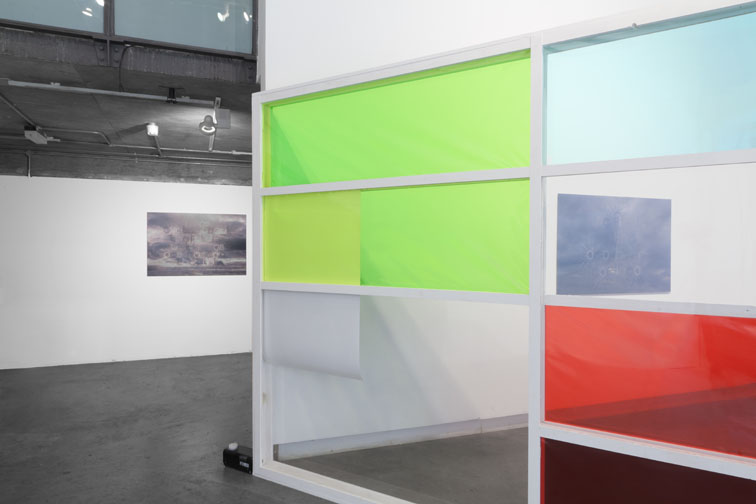 """Cultural Production/Cultural Erosion, 2013. Transparent vitrine wall which fills with smoke obscuring the images housed within. Acyrlic sheet, wood, paint, c-type prints. 16' x 10' x 4"""".  Installation p  hotograph by Davey Moor."""