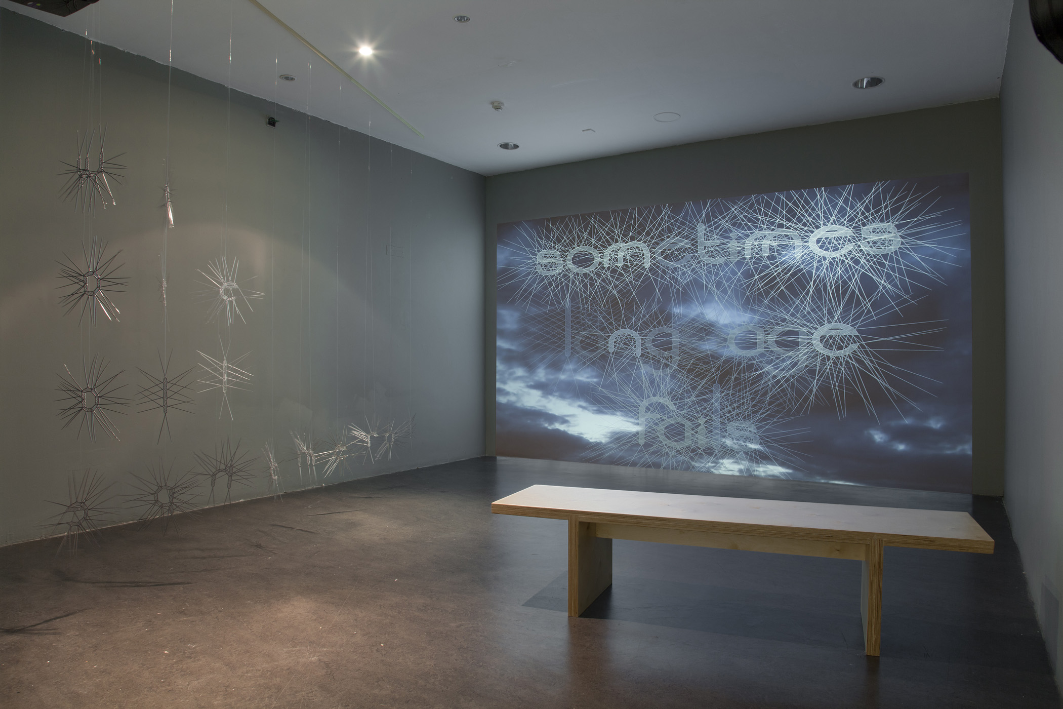 """We Are All Ephemeral, 2015. (left) Curtain of customized lasercut mirrored acrylic letters. Variable Dimensions.  self erosion, 2013. HD video and animation. Duration 18'30""""  Installation photography by Davey Moor."""