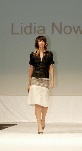 Black short sleeve button down top with light beige skirt.