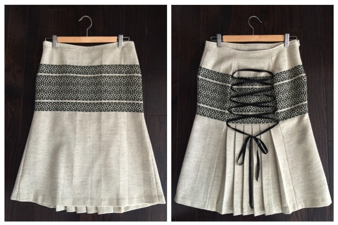 Wool beige fabric with black print on hip area. Pleated lower back panel with criss-cross ribbon detail. Polyester lining on inside.