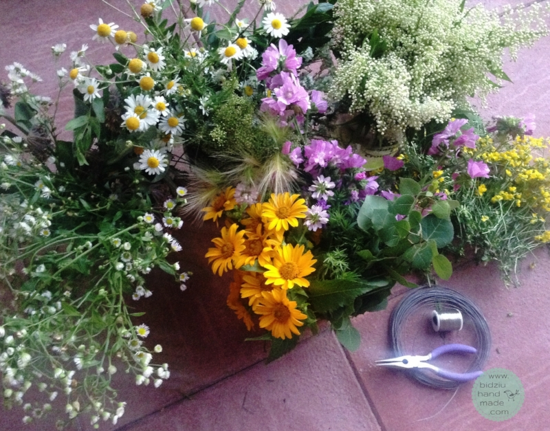 Assortment of grasses, leafy twigs, and wild flowers ready to be transformed into pretty flower crowns.
