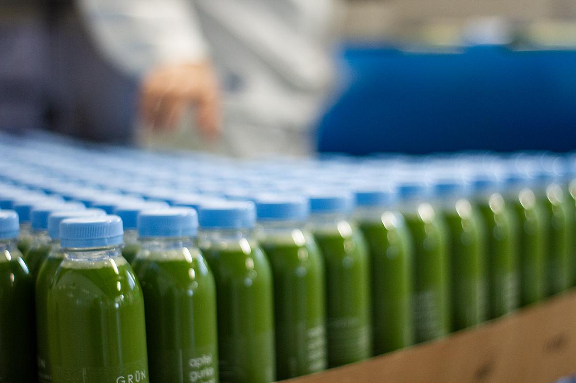 Die Säfte werden palettenweise transportiert und per Hand in die blauen HPP-Gefäße verladen.