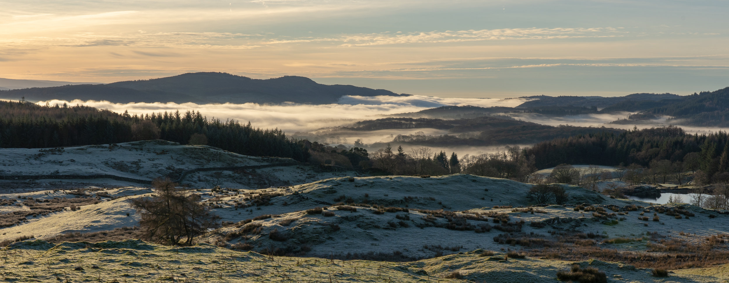 "Cloud Inversion over Windermere from Wise Een Tarn, December 2018.   f/14, 1/100 sec, 51mm   Some of my favourite shots have been taken from nearby Moss Eccles or Wise Een Tarn. On Christmas Eve I woke up early and saw the forecast on the ""Clear Outside"" app which told me that staying in bed would be a bad idea :). After hiking up the track I waited near Wise Een for the sunrise and searched for a composition north towards Langdale. However, thankfully I also turned around and saw this cloud cover over Windermere."