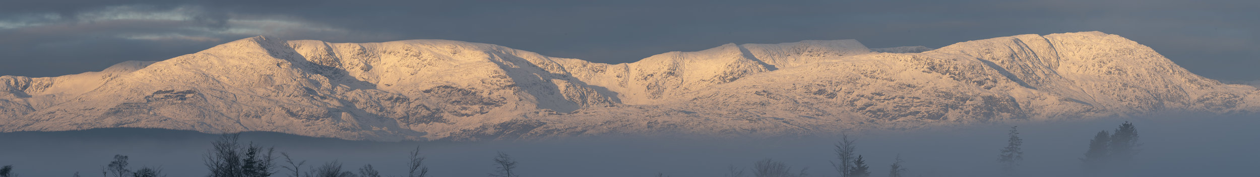 Mountains in the sky, 20th Jan 2019   f/13, 1/40 sec, 265mm (20 shot stitched panorama)   All of the Coniston and Langdale Mountains lit up at sunrise on the morning of 20th Jan, 2019. The cloud was lying low so the mountains were often isolated in their sky islands. A lot of shots to process, as you might imagine, but thought I'd start with this 20 shot panorama taken at 265mm. The source file of this one is 32086 x 6224 pixels, so I'm planning a 4+ metre print of this… 😁!!