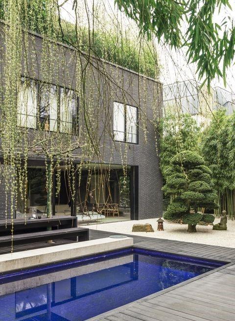 Спокойно външно пространство - АрхитектътМарк Мейре проектира тази къща за семейството си в Кьолн, Германия. Басейнът е облечен в италиански плочки, пейката и декингът саот тъментик, а дървото е внесено от Япония.
