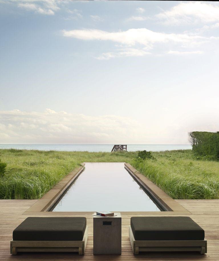 Скривалище в тревата - В това ваканционно жилище в Хемптънс, което Тимъти Хейнс и Кевин Робъртс проектират за младо семейство, високи треви обграждат плувния басейн с широка гледка към Атлантическия океан. Табуретките са от тиково дърво (продукт на Sutherland),покрити с възгравници във флорални мотиви, ациментовата маса е от каталога на CB2.