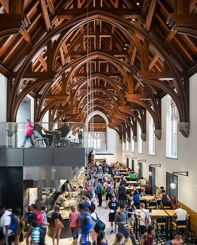 """Sometimes called """"The Gothic Wonderland"""", the renovation of Duke University's historic West Campus strikes a balance between traditional and contemporary design. The collegiate gothic style bows to the building's historic legacy with suspended balconies and oak trusses in the Great Hall (pictured here). ———————————————————— Project: West Campus Union, Duke University, NC Architect: Grimshaw (@grimshawarch) Ceiling/Wall Product: Wood beams, louvers, linear planks, and perforated panels by ACGI ———————————————————— 📨 To learn more about how we helped bring this to life - or for more information on wood ceiling/wall systems - contact Design Strategies: @designstrategies"""