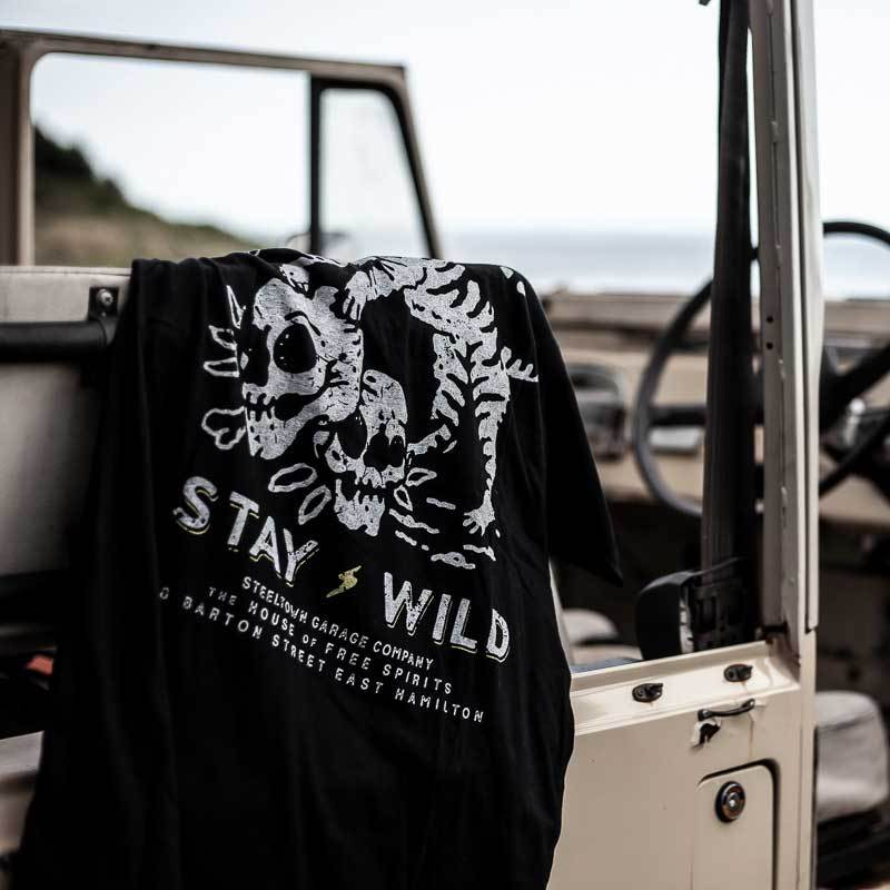Stay-Wild-Tee-Steeltown-Garage-Black-Hanging_2048x2048.jpg