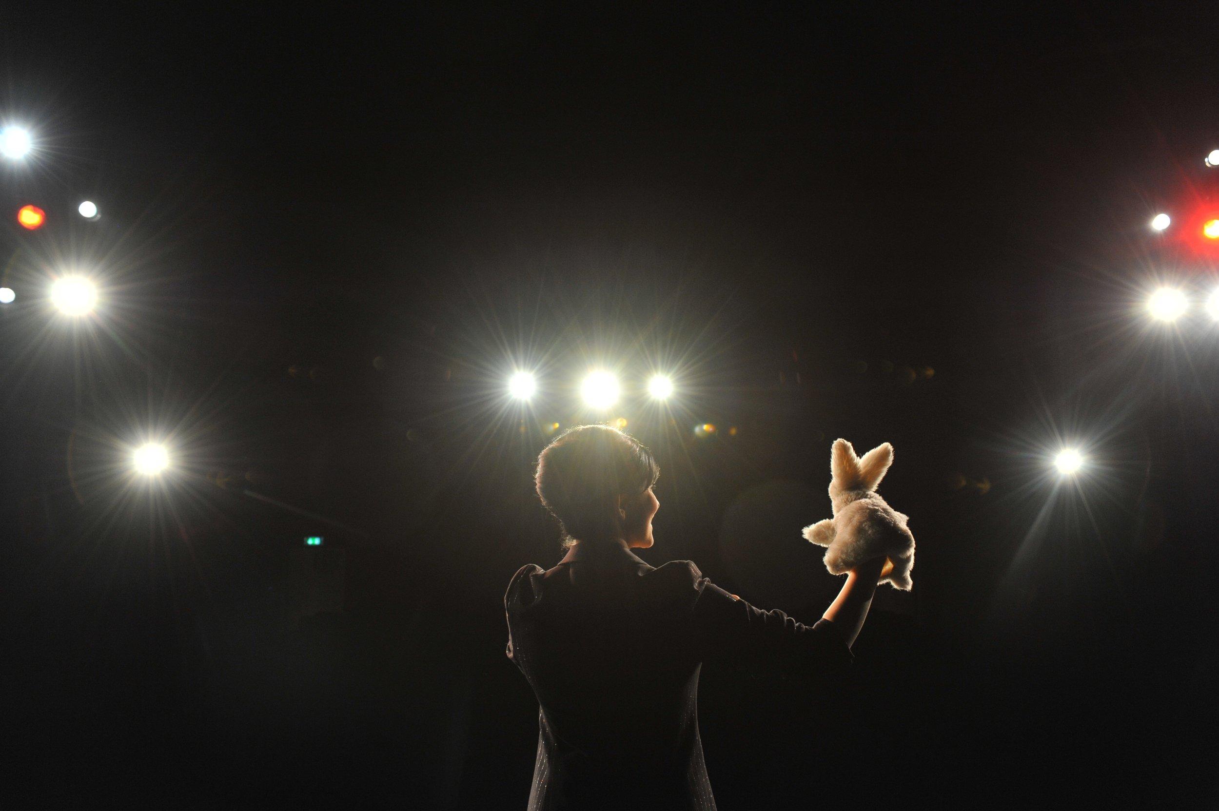 Bühnenshow - Ob vor 20 oder 800 Zuschauern Michelle Spillner hat ihr Publikum sofort im Griff und sorgt für starke Momente mit Erinnerungswert. Michelles Zauberkunst ist stilvoll, charmant, witzig, geistreich und intelligent. Das Kaninchen ist ihr ständiger Begleiter, keine Show ohne Kaninchen - aber anders, als Sie es erwarten mögen. Die Zauberkünstlerin weiß, dass sich in jedem Publikum mindestens ein Medium befindet und sie weiß sich das zu Nutze zu machen.In einer riskanten Wette geht es um eines ihrer schwierigsten Kunststücke. Es ist so schwierig, dass sie selbst gar nicht hinschauen kann – was es umso schwieriger macht. Bei diesem Spiel mit dem Unerwarteten wird ein Zuschauer zum Handicap, und trotz ungewohnter Einsichten über die Schulter der Künstlerin erhält selbst er keinerlei Hinweise auf das Trickgeheimnis.Und wenn Michelle einem Gast (oder auch dem Chef, dem Geburtstagskind, dem Verkäufer des Jahres...) sprichtwörtlich unter die Arme greift, dann wird er mit einem eigenen magischen Act zum Zauberstar vor großem Publikum.All das auf Michelles ganz eigene Art, mit unverwechselbarem Humor und augenzwinkerndem Charme.Michelle ist international tätig, trat beim Comedy-Festival in der Schweiz auf, ist regelmaßig zaubernder Gast in Varieté- und Galashows, in Comedy-Clubs, auf Firmenevents und Kick-off-Meetings und wird von international operierenden Unternehmen für Auslandsauftritte engagiert.Ihrer Bühnenshows können zeitlich angepasst werden und umfassen zwischen 15 und 60 Minuten.