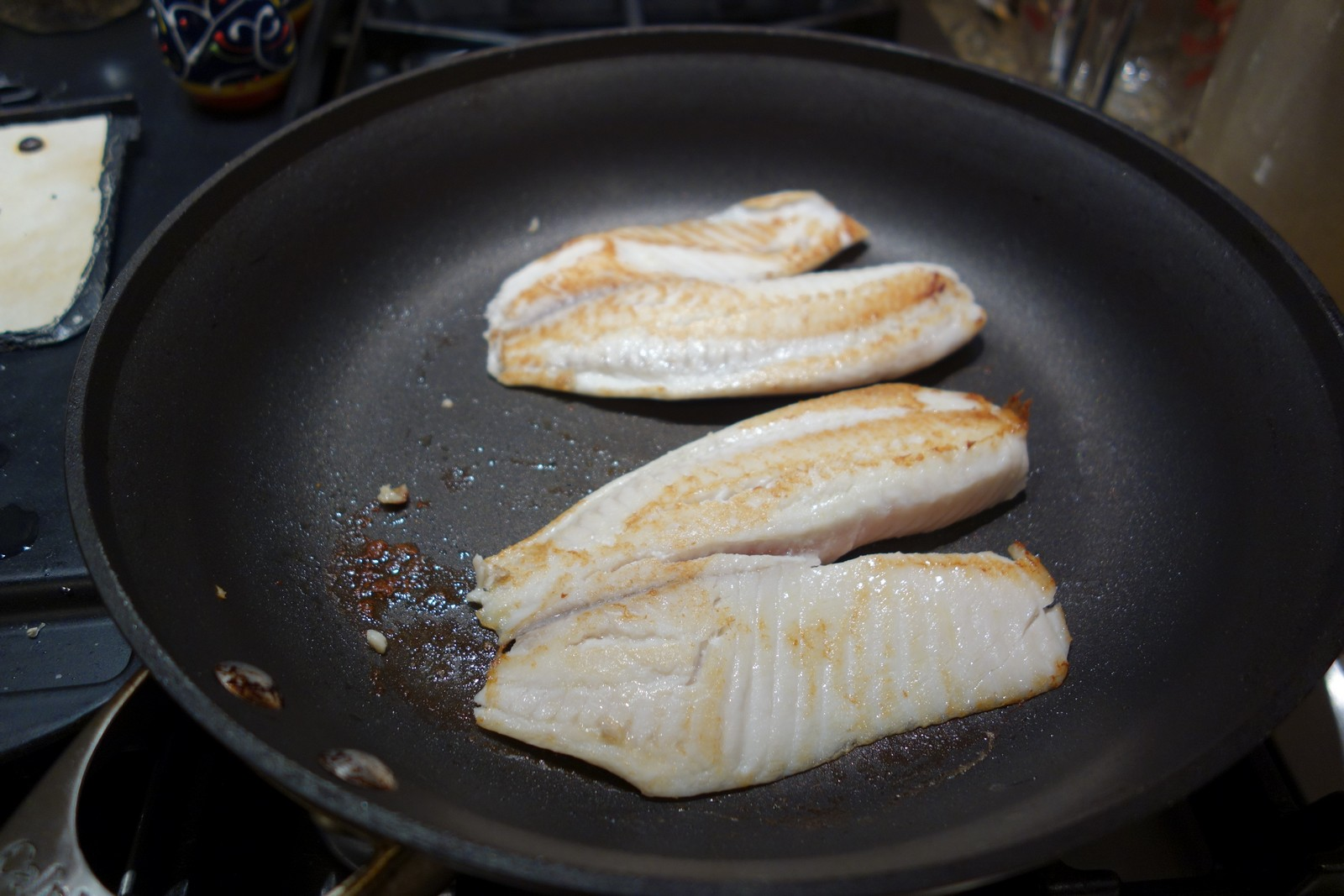 2 Tilapia filets in a large skillet with only a coating of butter. They brown well on medium-high heat, even in a non-stick skillet.