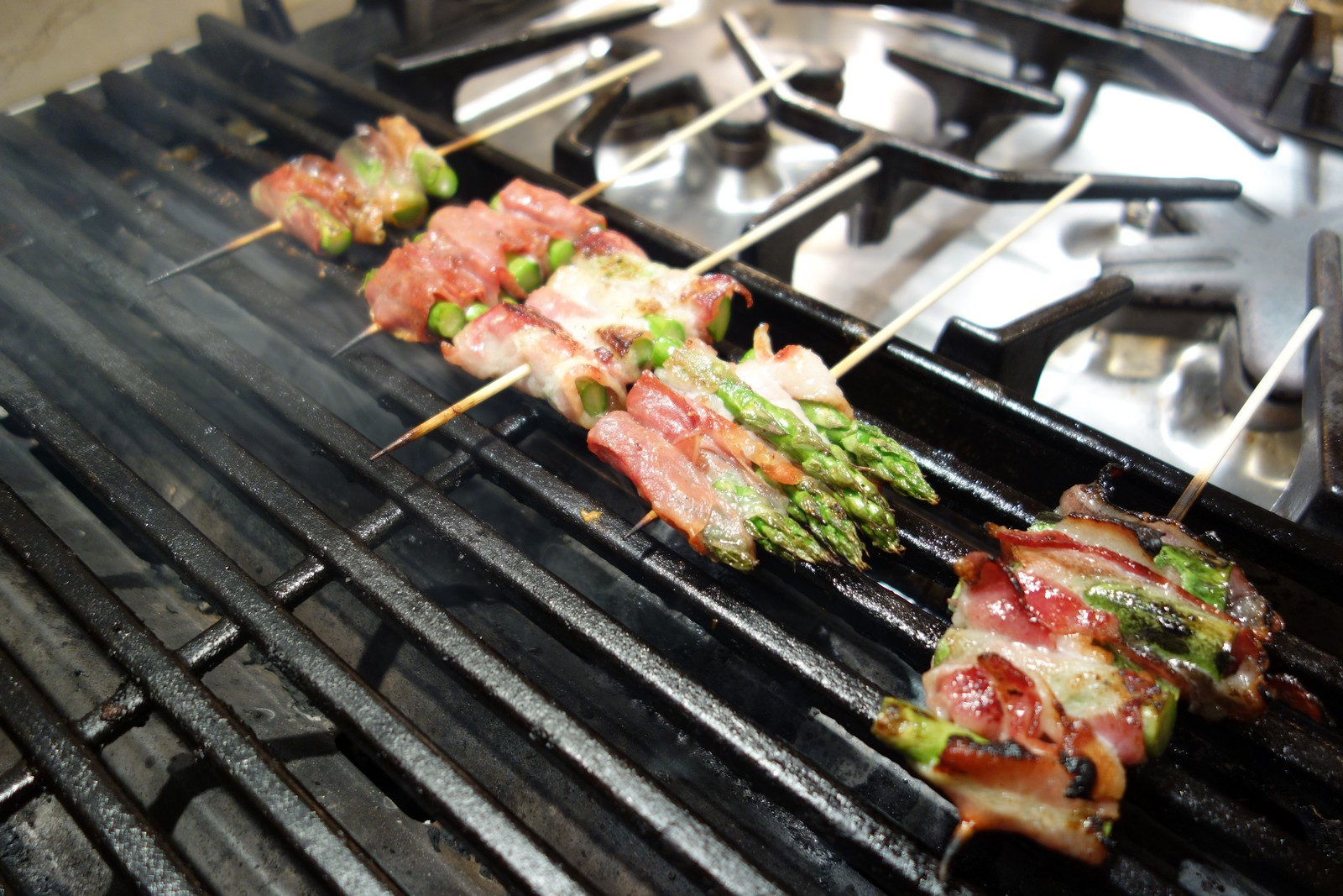 Grill over medium-high or high heat. Leave the ends of the skewers hanging off the grill so you can use them to flip the asparagus.