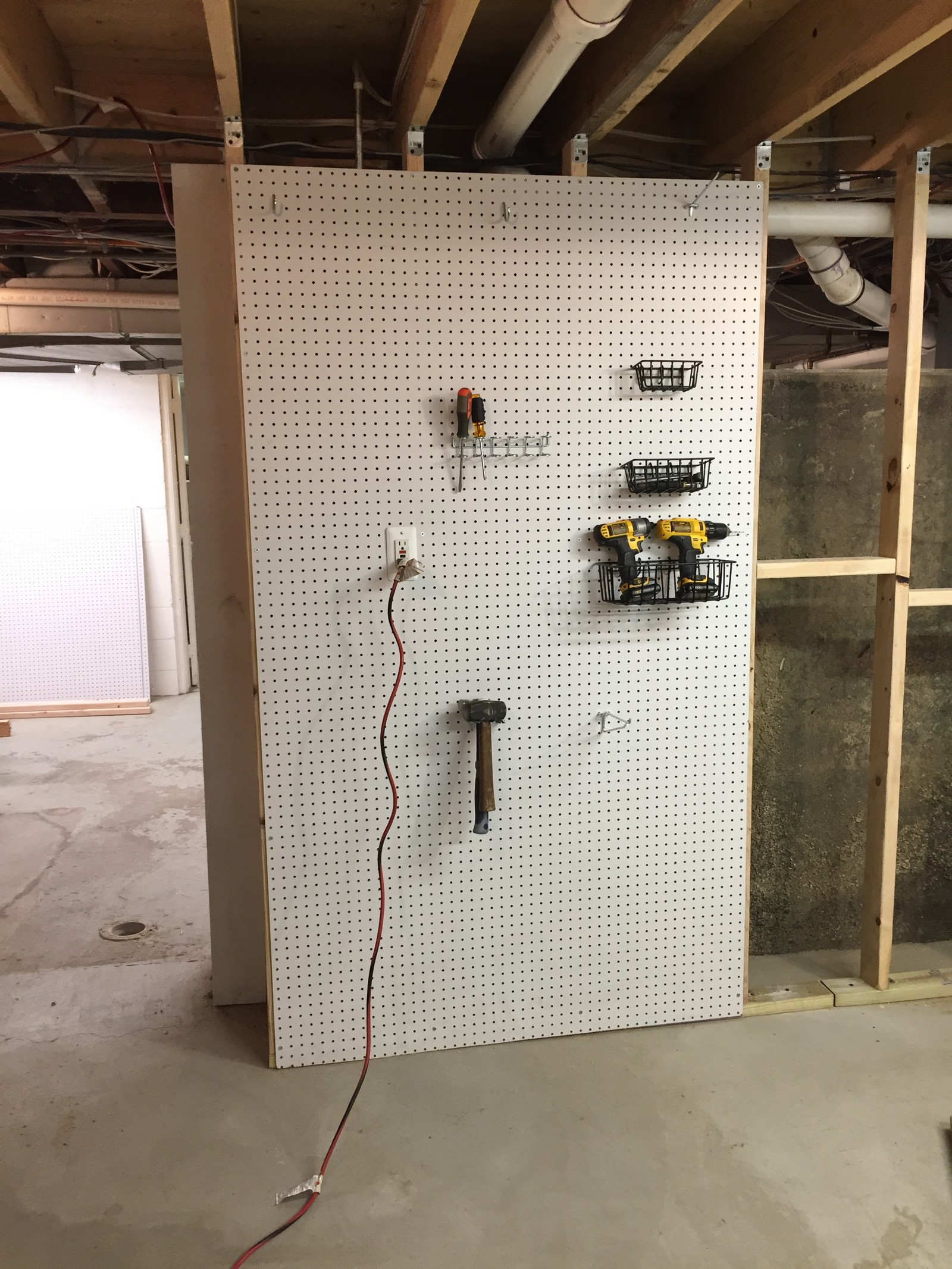 """With 16"""" spacing between each stud, I was able to mount each 48"""" wide sheet of pegboard to a joist so that the end of each piece was on a stud. That helped a lot with strength when attaching tools to the boards. I also mounted an electrical outlet to one of the joists so that it was accessible on the wall. Finally, I made cut-outs in the wall so I could remove pieces of the panel for access to the sewer or water lines."""