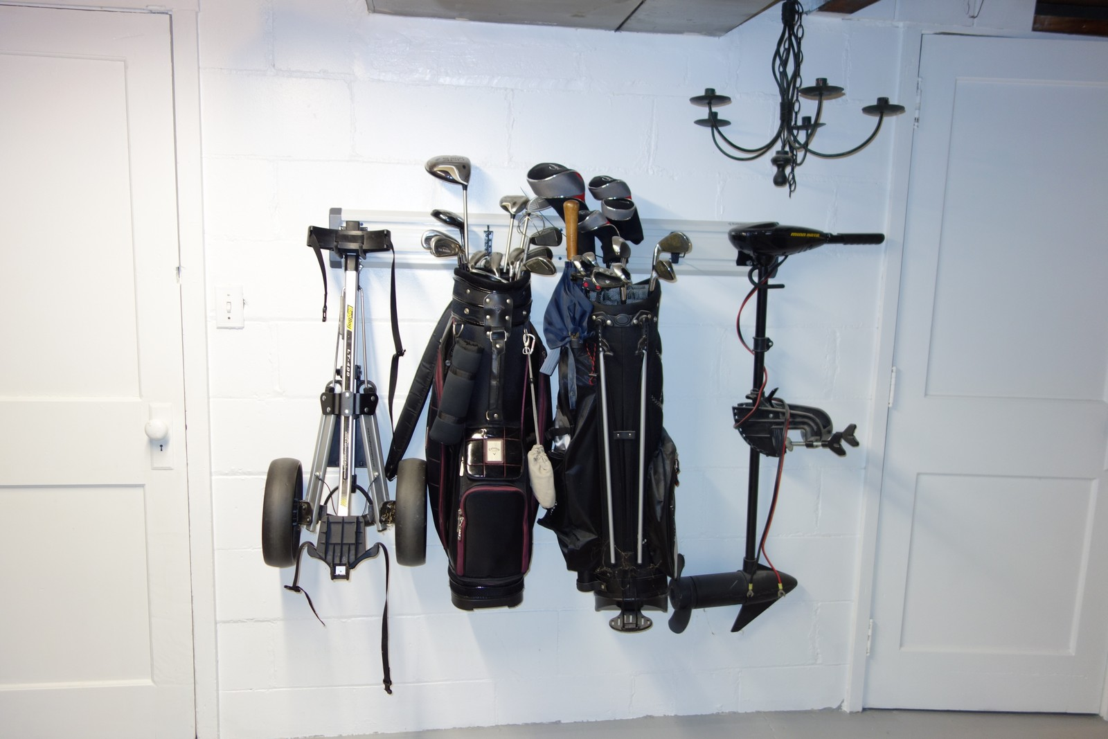 "Get those golf bags off the ground and away from basement critters. Geartrak holds a lot of weight easily when properly mounted. The two golf bags and electric boat motor above all weigh ""a lot""."