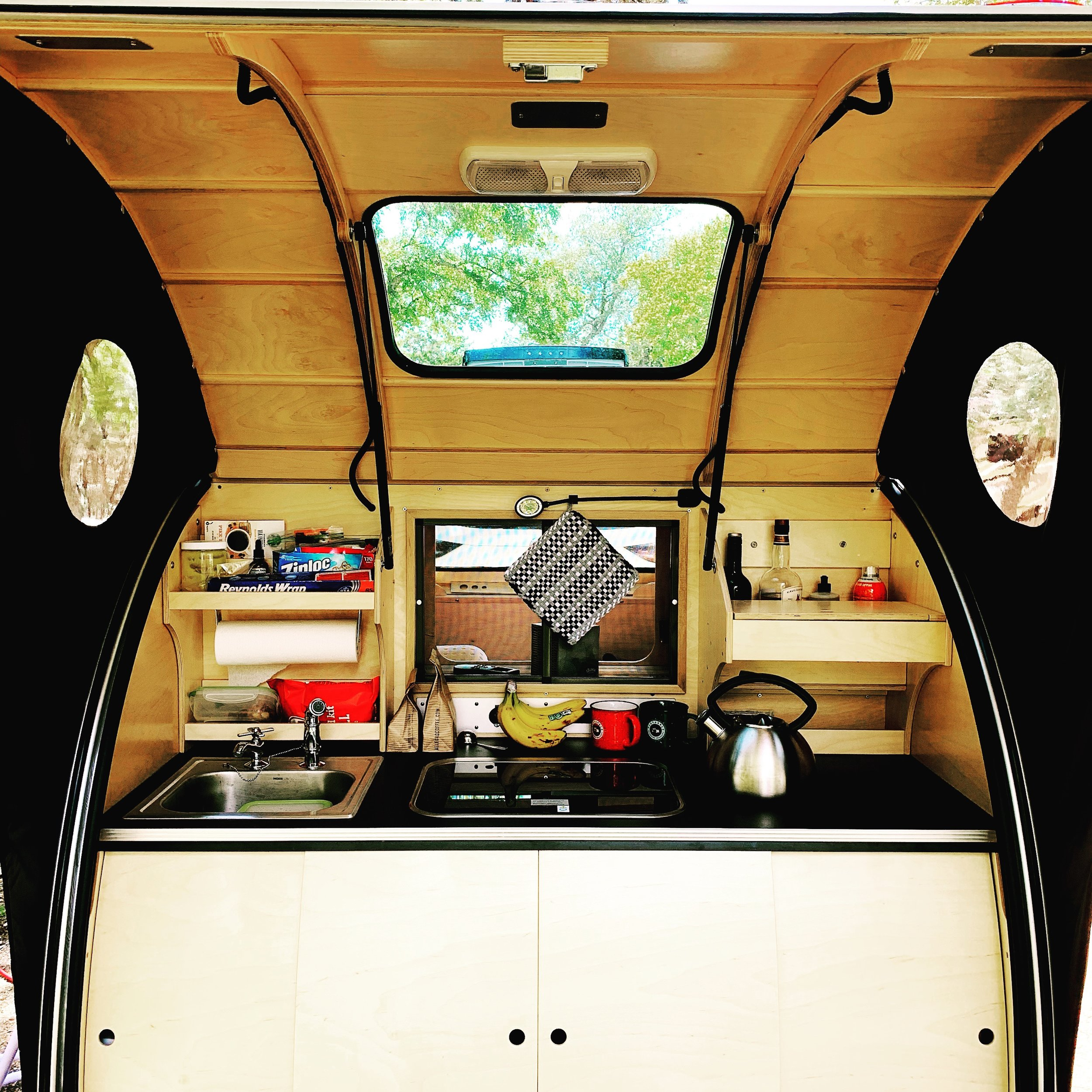 "- ""The Vistabule's robust galley kitchen covers all the essentials and adds a unique pass-through that lets whoever is manning the kitchen chat, serve a cocktail, or share dinner with the person inside the trailer."""
