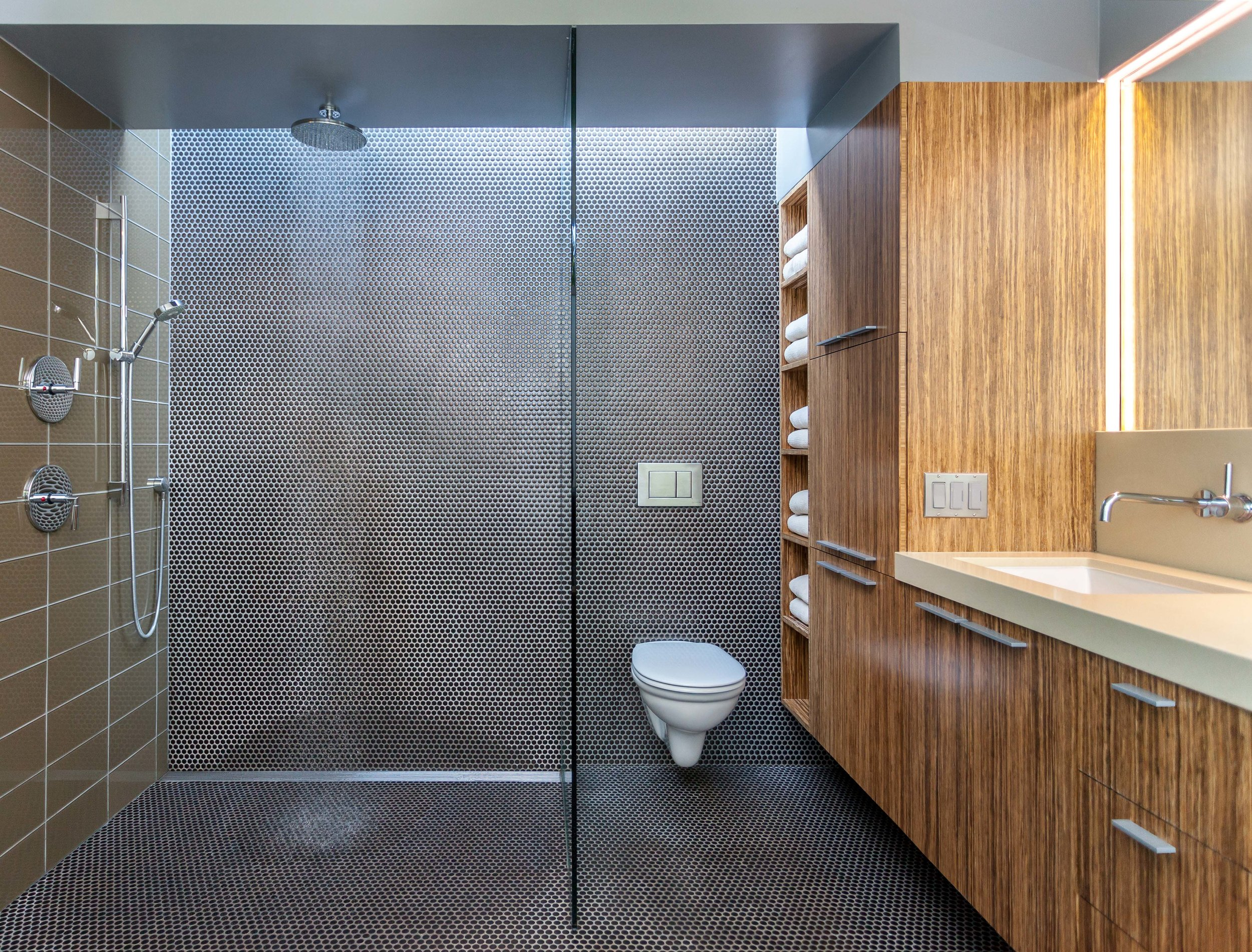 Open shower room with glass divider. The cabinet hovers over the floor and the recessed LED lights the mirror.