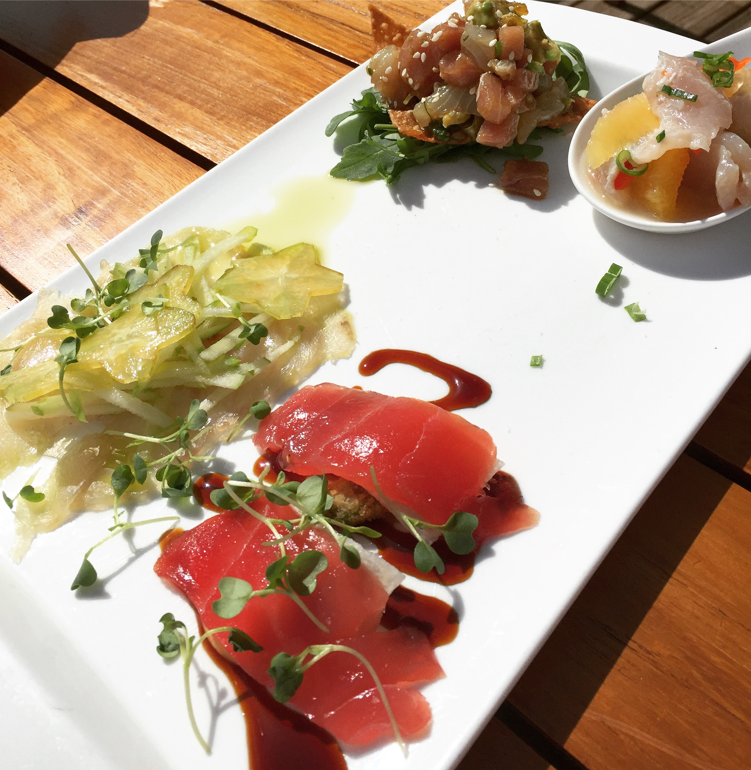 Catch Tasting Plate (clockwise from bottom left): tuna sashimi, local crudo, tuna & wahoo tartare & fresh catch ceviche