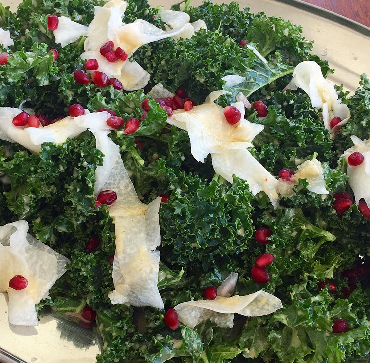 Kale salad with pickled jicama and pomegranate tossed in a lemon thyme season pepper vinaigrette