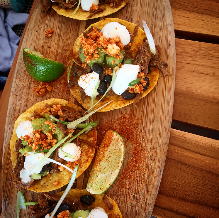 Beef Tostados topped with spiced queso, black bean puree, salsa verde, lime crema and cilantro