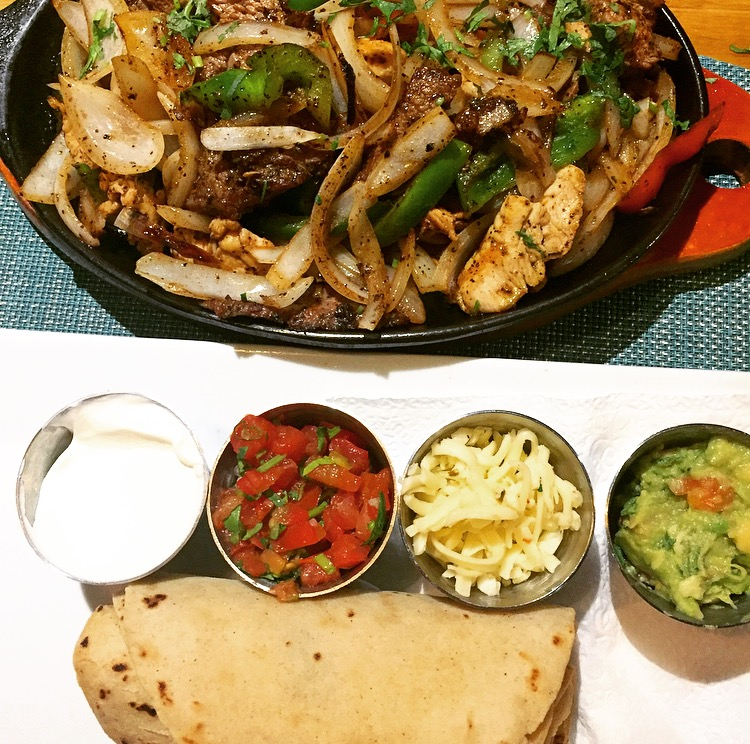 Sizzling Fajitas: chicken & flank steak combo sauteed with onions, chile mojo and bell peppers. Smother some sour cream, pico de gallo, pepper jack cheese and guacamole on your flour or corn tortillas.