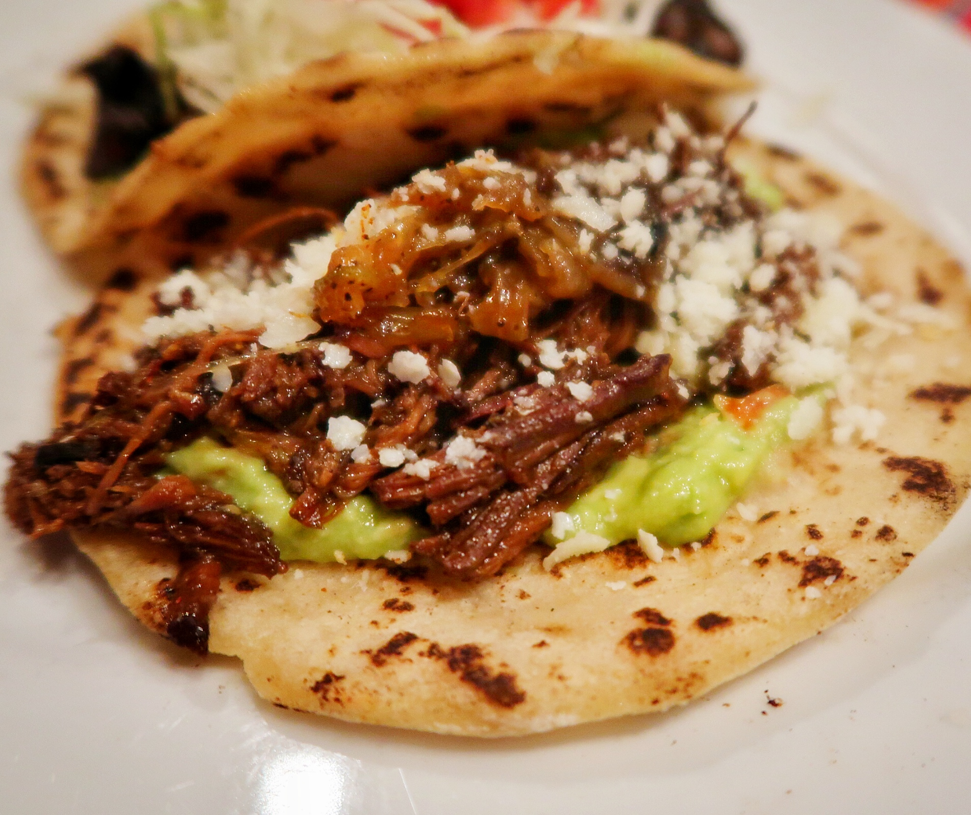 Beef Barbacoa taco - Tender house smoked beef brisket rubbed in ancho chile rub, caramelised onions, cotija cheese and guacamoles on a corn or flour tortilla