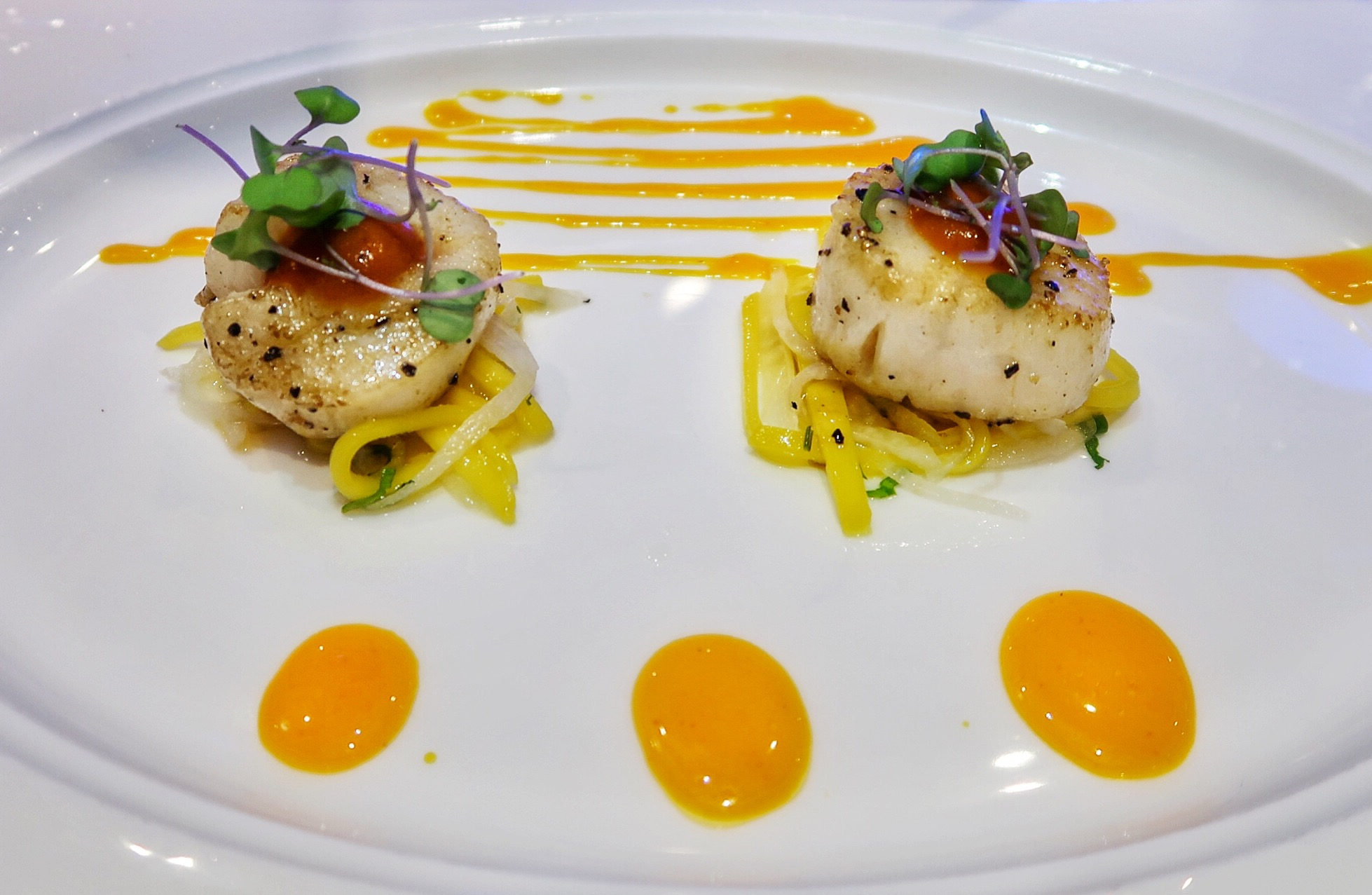 Clay oven roasted diver sea scallops with a grilled mango and pickled jicama slaw, tomato chutney and chili mandarin drizzle.