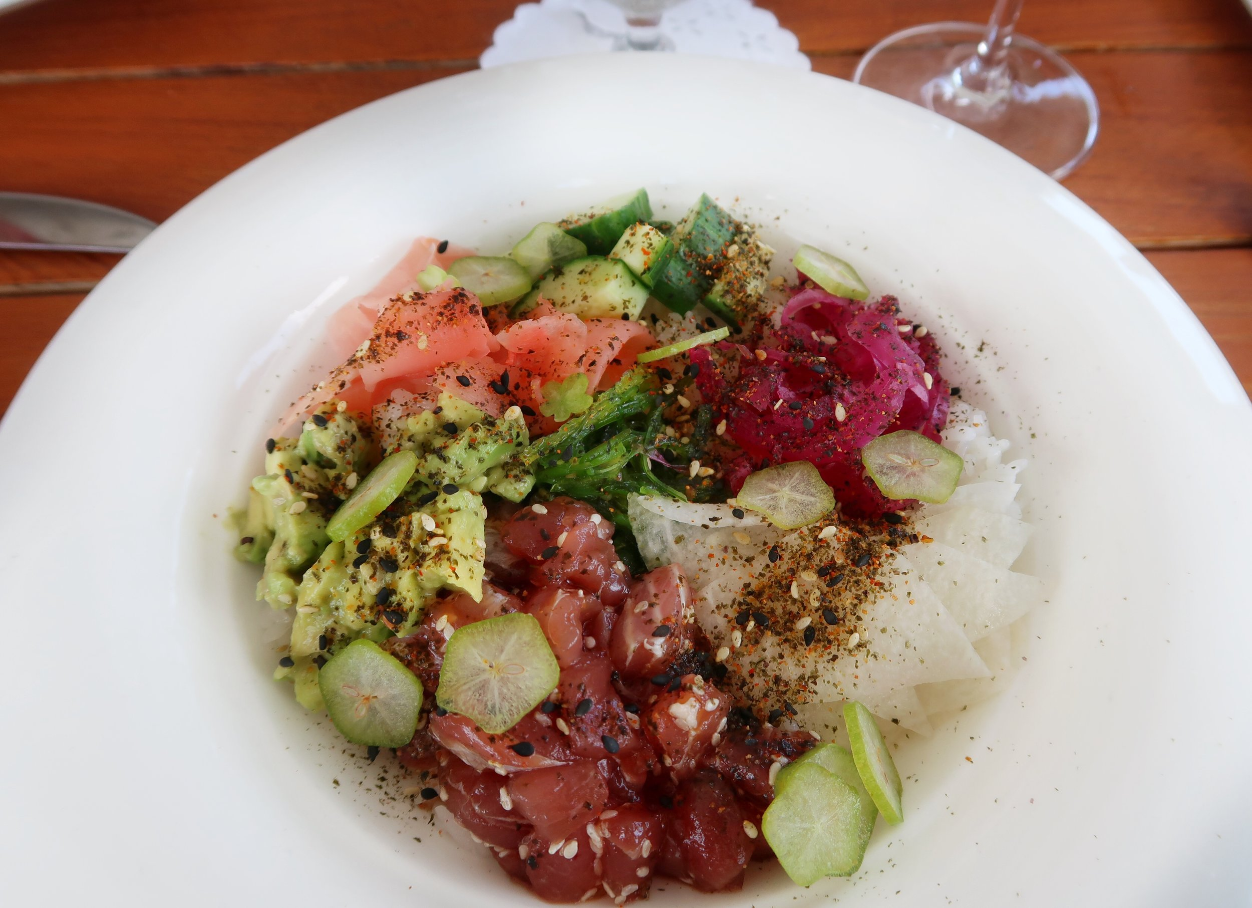 A refreshing and light Tuna Poke Bowl - Yellowfin tuna, rice, wakame seaweed salad, avocado, pickled vegetables, furikake and herbs.