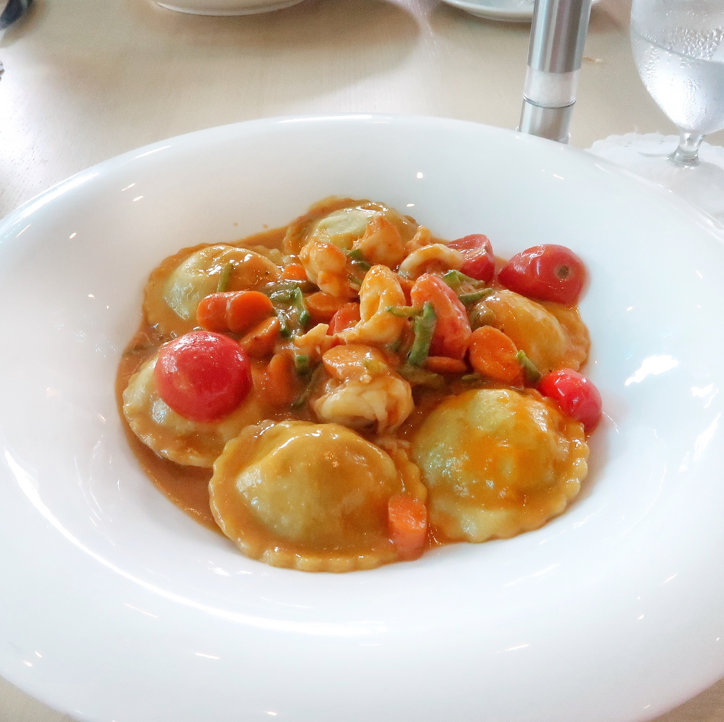 "The ""Ravioli"" filled and topped with shrimp & Caribbean lobster and served with a sauce consisting of vermouth, summer vegetables, ginger and aromatics."