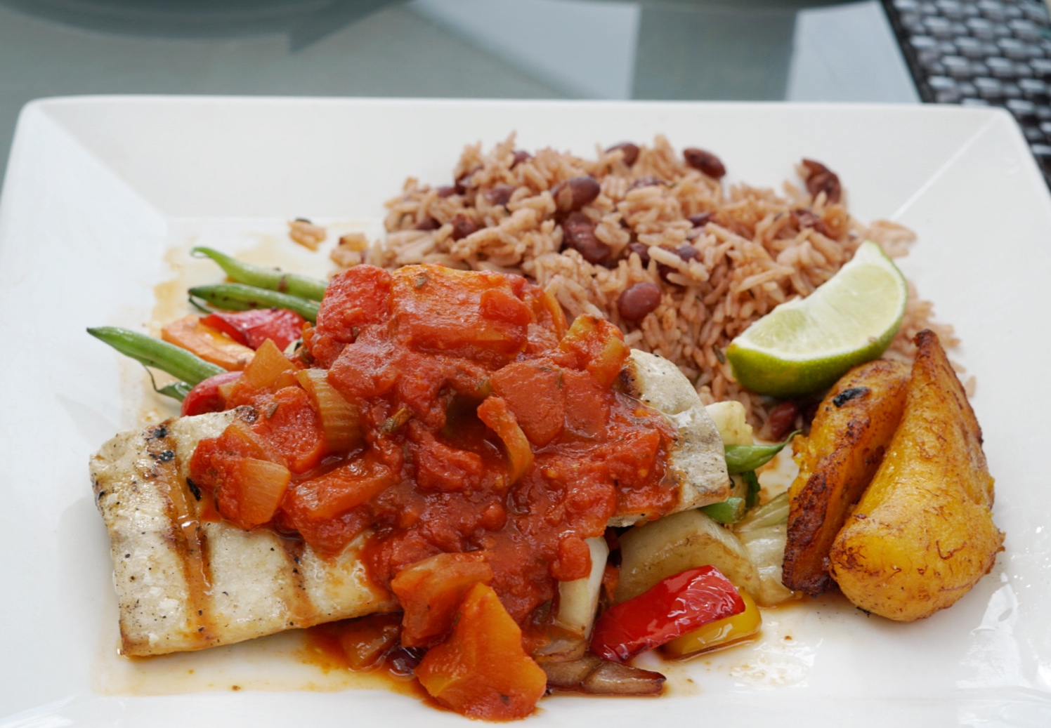 Cayman Style Mahi topped with a tomato-based sauce and served with green beans, sweet fried plantains and rice & beans