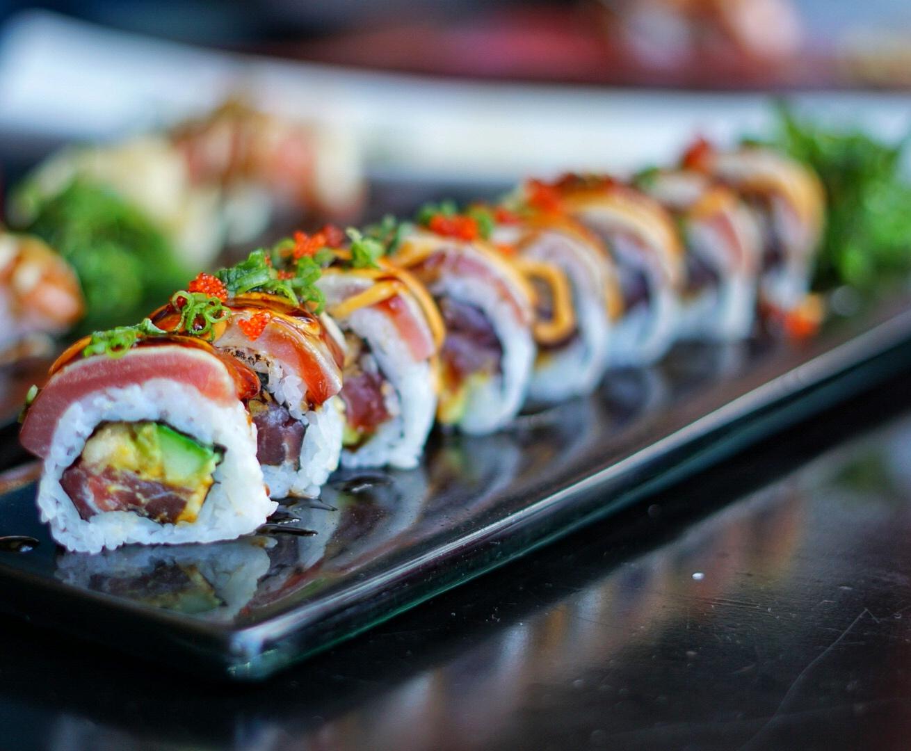 Spicy Tuna Tataki: Ahi tuna poke, Haas avocado, cucumber, homemade spicy sauce, soy BBQ sauce, orange tobiko & tempura flakes.