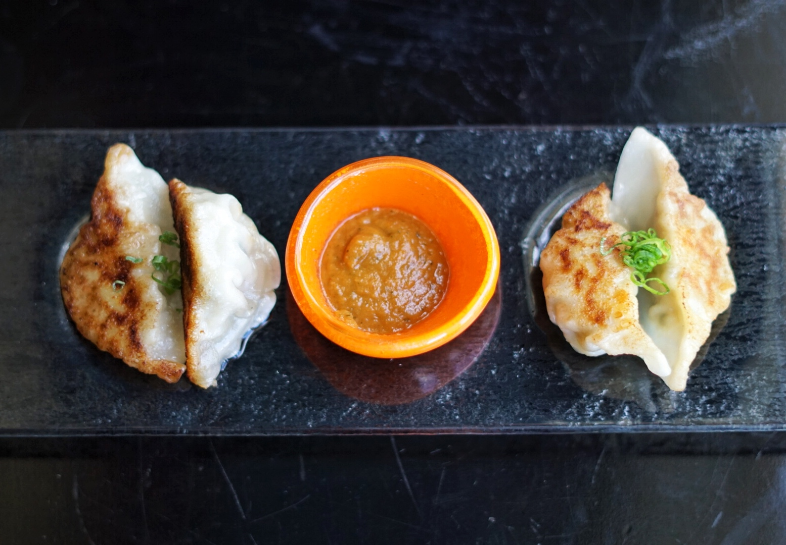 Classic Gyoza: pan-fried chicken dumplings served with a ginger chili soy sauce