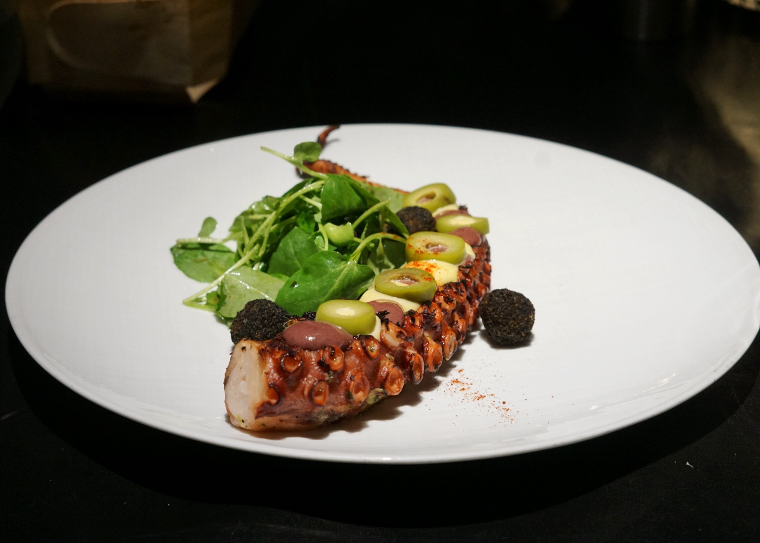 The tender Grilled Octopus is served with chimichurri, olive sauce, aji amarillo aioli and squid ink potato croquettes.