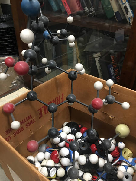 A wooden ball and stick model of Aureomycin lies in a parts box along with plastic atoms and molecular fragments from disassembled models gathering dust as they fruitlessly await incorporation into new models.