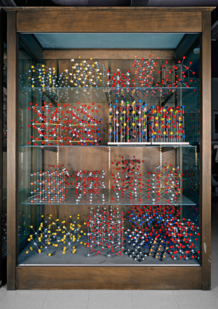 A display case showing various ball-and-stick models; the different colors represent different elements. Most are common minerals and were manufactured by the Leybold company for teaching purposes. On the left side of the third shelf down can be seen a model of cubic NaCl (table salt) with alternating red and silver spheres. On the left of the second shelf down are two models of quartz (SiO2) illustrating the non-superimposable mirror images of left- and right-handed quartz.