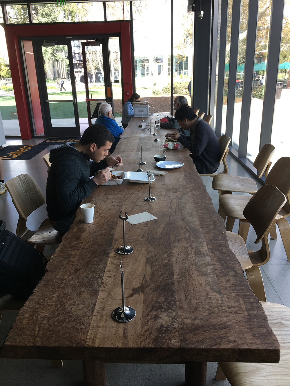 Diners eat lunch at the long table made from the wood of Caltech's famed Engelmann oak.