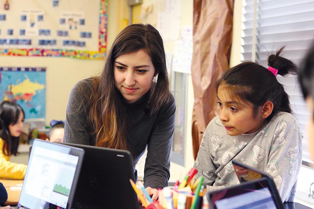 Caltech senior Anna Resnick shares basic coding skills with Natalia Jimenez at Pasadena's Jefferson Elementary School.
