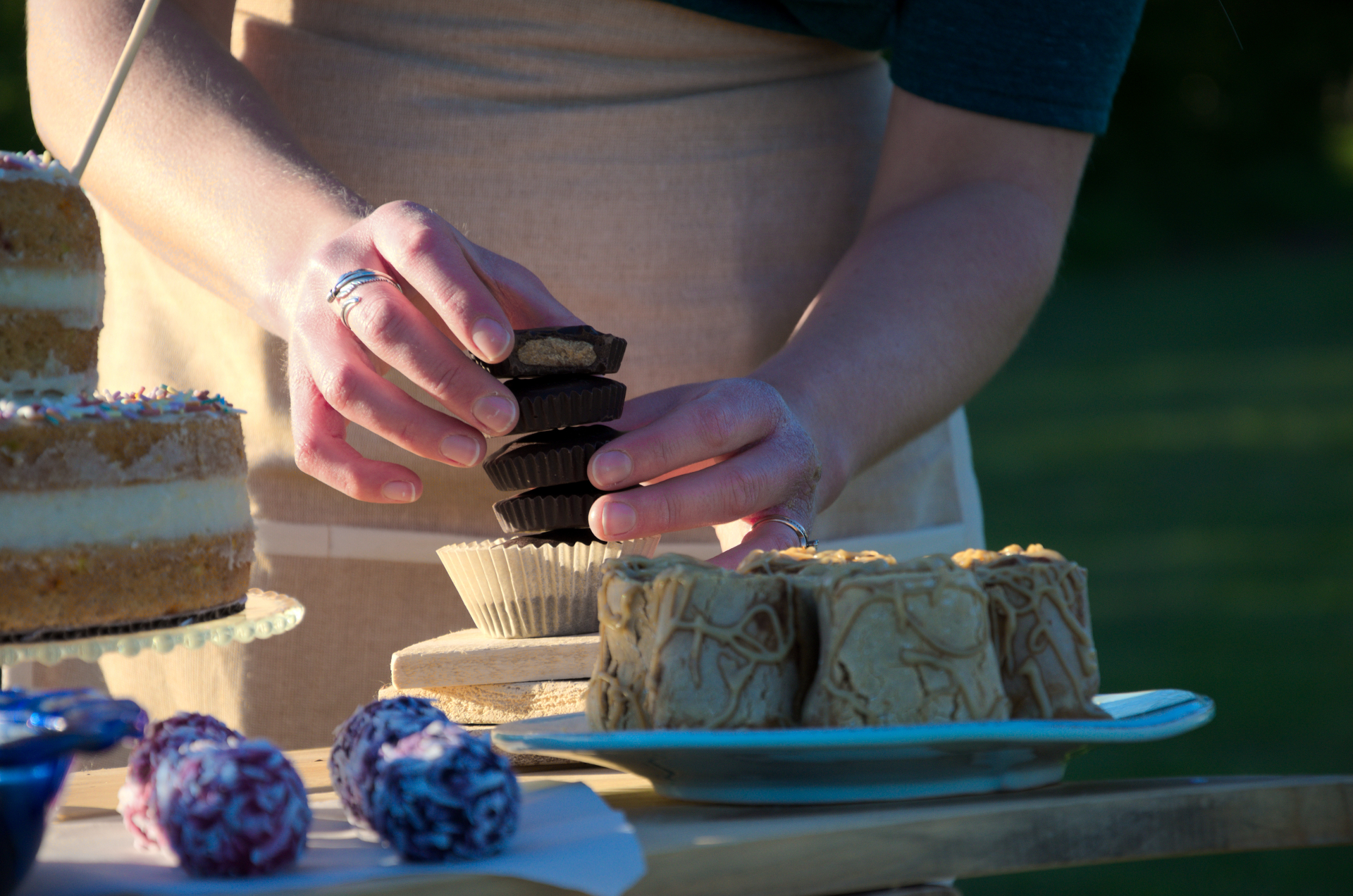 Here's me stacking some tasty Peanut Butter Cups with a Cinnamon Roll Cake and other healthy desserts on the table