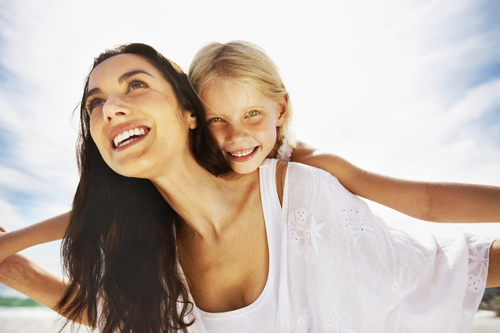 Woman smiling big with perfect teeth and daughter on her back at a Santa Barbara beach