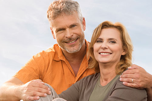 Middle aged couple sitting on a beach with blue skies smiling confidently.