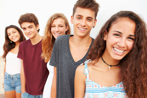 Five teens at the beach smiling showing nicely aligned teeth.