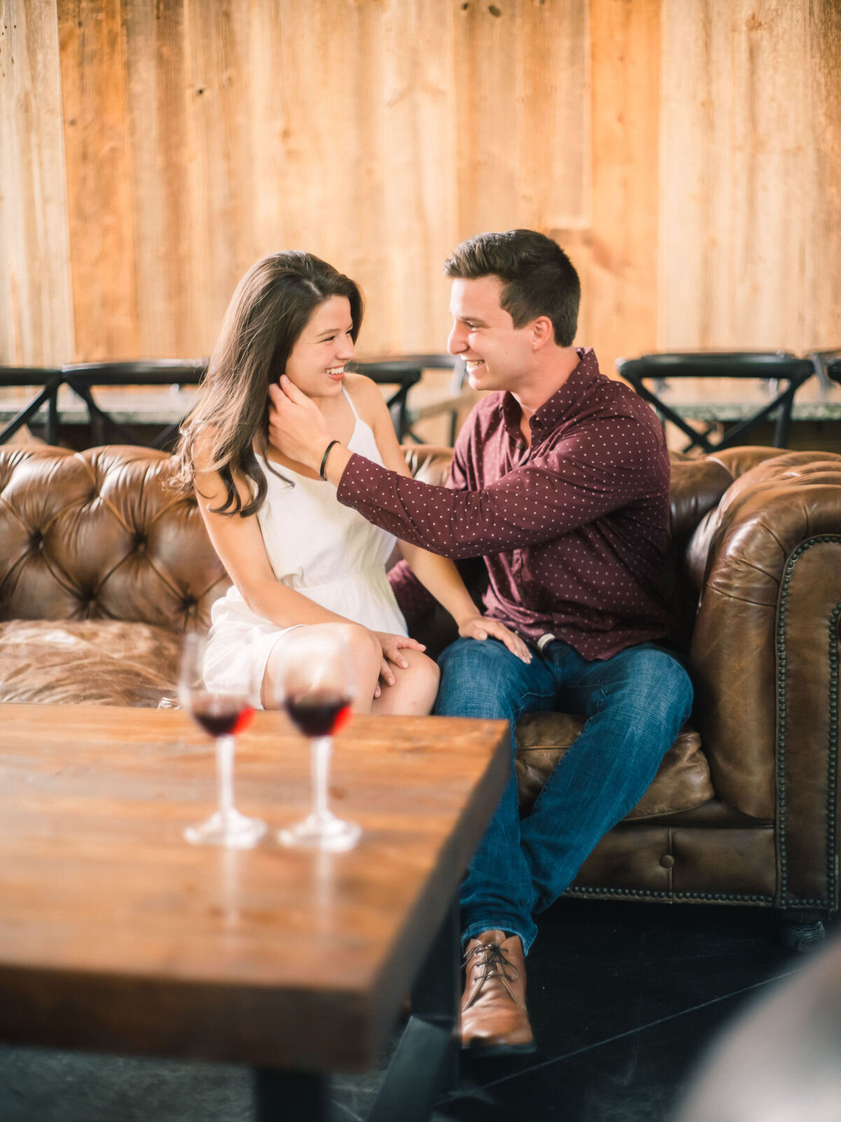 couple sitting on a couch with man reaching across to touch woman's face with wine in front of them smiling and laughing
