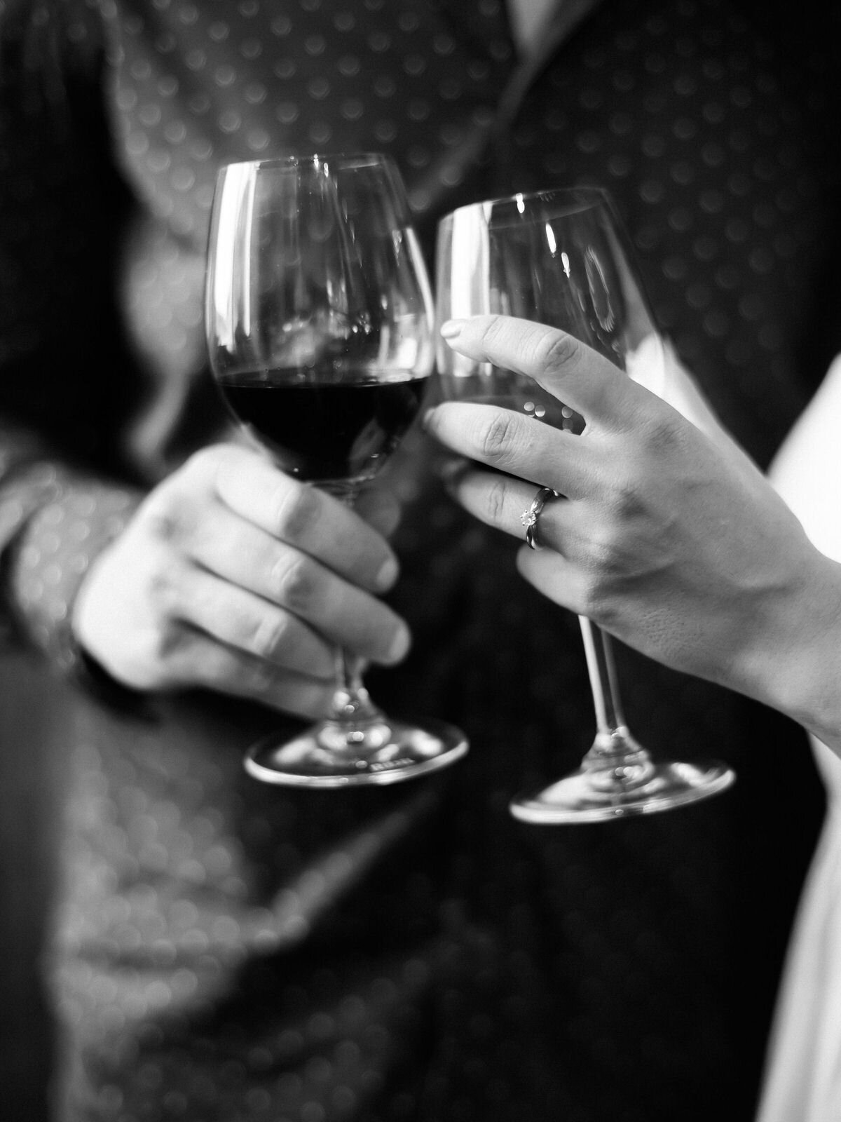 wine glasses in black and white with an engagement ring touching with a couple behind them toasting